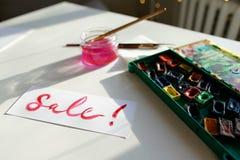 水彩在白色纸片的题字销售,在桌上 图库摄影