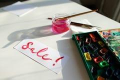 水彩在白色纸片的题字销售,在桌上 免版税库存图片