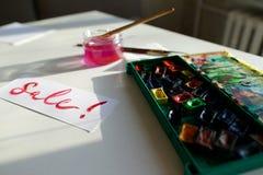 水彩在白色纸片的题字销售,在桌上 库存图片