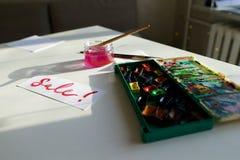 水彩在白色纸片的题字销售,在桌上 库存照片