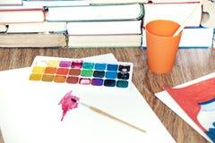 水彩油漆,刷子很好使用了和纸片在木桌上的与堆书背景 库存图片