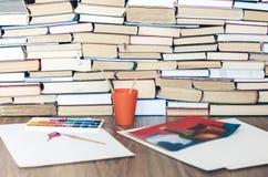 水彩油漆,刷子很好使用了和纸片在木桌上的与堆书背景 免版税库存图片