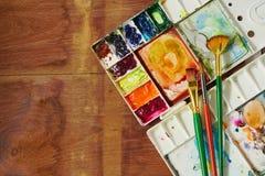 水彩调色板与刷子各种各样的大小的在木纹理背景 图库摄影