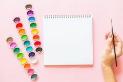 水彩调色板创造性的平的位置,笔记本,拿着画笔的女性手 桃红色柔和的淡色彩的艺术家工作场所 库存图片