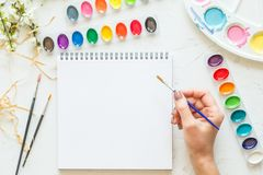 水彩调色板,白皮书和女性手创造性的平的位置拿着画笔的 灰色混凝土的艺术家工作场所 图库摄影