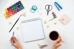 水彩,刷子,与空白页,妇女拿着茶的` s手的写生簿和brushpen和其他固定式供应 免版税库存照片