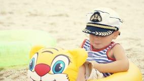 水手服的小白种人男孩和盖帽坐在游泳的海滩敲响和笑 库存图片