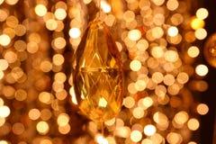 水晶枝形吊灯线的抽象图象金刚石装饰在金光bokeh的 免版税库存照片