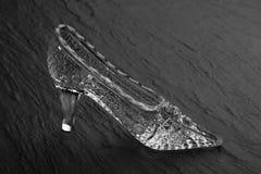 水晶玻璃在黑暗的石背景的灰姑娘鞋子 免版税库存照片