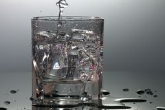 水晶玻璃用水和冰柱填装了 免版税库存图片