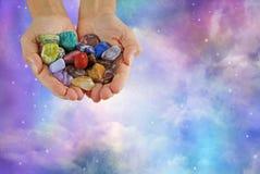 水晶翻滚的医治用的石头的愈疗者提供的选择 免版税库存照片
