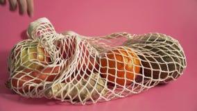 水果和蔬菜在滤网袋子,供选择到塑料购物带来在桃红色背景4k 股票视频