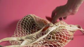 水果和蔬菜在滤网袋子,供选择到塑料购物带来在桃红色背景4k 影视素材