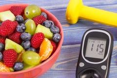 水果沙拉、glucometer检查的糖水平和哑铃,健康生活方式和营养概念 库存照片