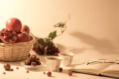 水果篮、日期在一个银色碗,阿拉伯茶杯有开放书的和放大镜 免版税库存照片
