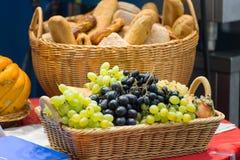 水果篮和面包篮子在桌上 库存图片
