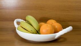 水果钵用香蕉桔子和猕猴桃在桌上 免版税库存图片