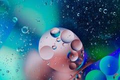 水油泡影宏观抽象背景流程液体蓝色桃红色白色水色 图库摄影