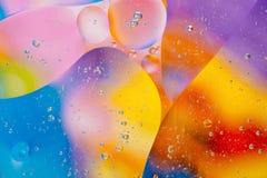水油泡影宏观抽象背景流程液体蓝色水色黄色桃红色红色 图库摄影