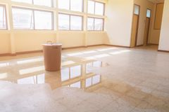 水泄漏从天花板和流程投下在红色桶的内部办公楼在磨石子地地板上 库存照片