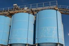 水泥的生产的大蓝色金属工业筒仓在一棵工业水泥植物的蓝天背景的  免版税库存图片