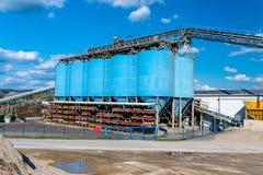 水泥的生产的大蓝色金属工业筒仓在一棵工业水泥植物的蓝天背景的  图库摄影