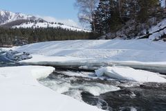 水流量在冰海岸中的熔化的河在山附近 库存图片