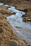 水流量的运动在沙子河中,小河山的  库存图片