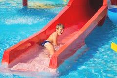 水滑道的愉快的快乐的白种人男孩在水色公园 图库摄影