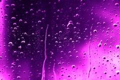 水滴在紫色玻璃的 库存照片