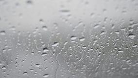 水滴特写镜头在玻璃,雨雨的,消失 在夏天阵雨期间,大雨下落触击窗玻璃 股票录像