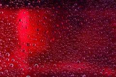 水滴红色表面上的 宏观抽象照片,背景, 免版税库存图片