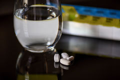 水玻璃和白色药片片剂特写镜头在黑背景 库存照片