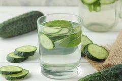水用黄瓜 刷新的饮食水用在一个玻璃杯子的黄瓜在轻的背景 戒毒所饮料概念 夏天刷新 库存照片