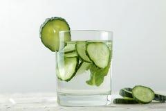水用黄瓜 刷新的饮食水用在一个玻璃杯子的黄瓜在轻的背景 戒毒所饮料概念 夏天刷新 图库摄影