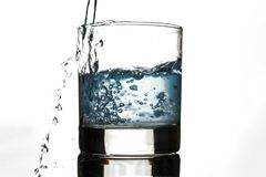水由在白色背景的玻璃倾吐 免版税库存图片