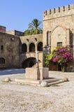 水的水源在骑士Hospitallers的背景的方形的Argirokastro的 罗得岛老镇,希腊 图库摄影