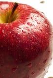 水的苹果接近的小滴红色 免版税库存图片