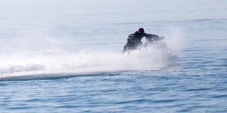 水的表面上的喷气机滑雪以的速度 库存图片