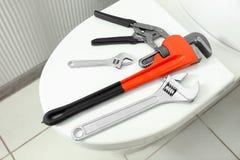 水管工在洗手间盒盖的` s工具 免版税库存图片