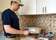 水管工在设施水槽前读了指示在厨房里 免版税库存照片