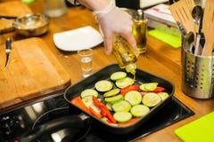 水罐倾倒在平底锅之上的液体有菜的 煎锅做准备 需要一些橄榄油 免版税库存图片