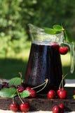 水罐用冷的樱桃汁,盖用小滴,在与叶子的一个甜樱桃旁边 库存图片