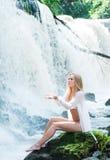 水背景的一名新白肤金发的妇女 免版税库存照片