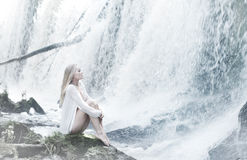 水背景的一名新白肤金发的妇女 图库摄影