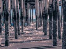 水色接触在码头下的在老果树园海滩 库存图片