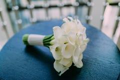 水芋属美丽的婚礼花束在蓝色桌背景开花 附庸风雅 在花束的软的焦点 库存照片