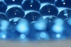 水蓝色胶凝体球 聚合物胶凝体 矽土凝胶 蓝色水凝胶球  与反射的水晶液体球 背景砖老纹理墙壁 图库摄影
