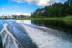 水表面上的泡沫似的足迹在快行汽艇后 湖塞利格,俄罗斯 免版税库存照片