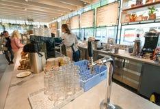 水轻拍在城市咖啡馆柜台的与菜单和访客的 免版税图库摄影